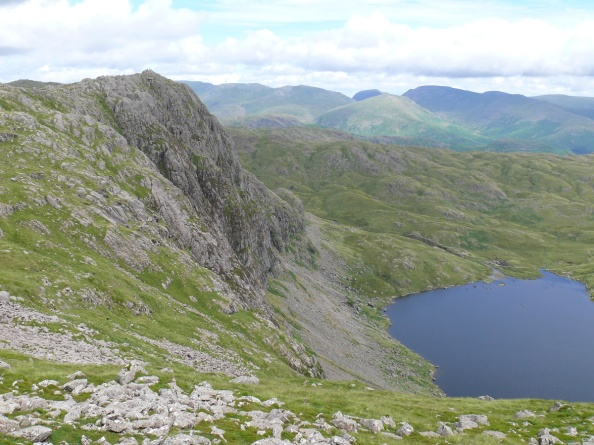 Heading round to Harrison Stickle with the vertical face of Pavey Ark over Stickle Tarn.