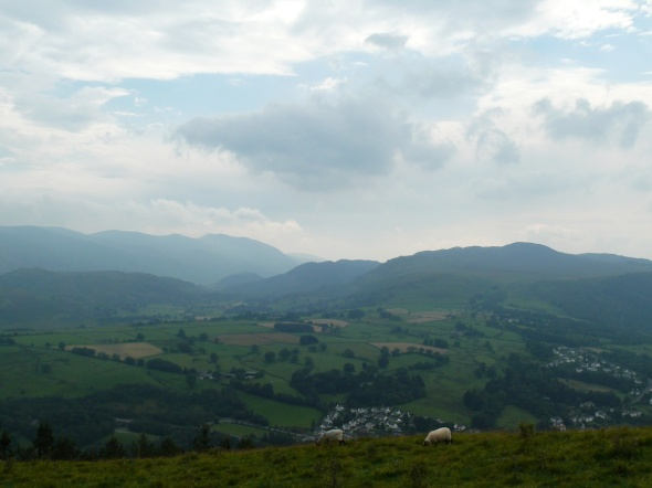Hazy Helvellyn beyond the dark looking Central Fells